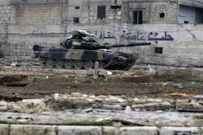 "A Syrian army tank is seen in front of a wall with Arabic that reads ""Aleppo is the capital of culture"" in the east Aleppo neighborhood of Tariq al-Bab, Syria, Dec. 3, 2016."