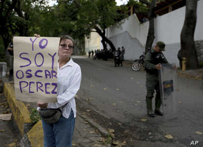 """A women who said she was a supporter of rebel police officer Oscar Perez holds a poster that reads in Spanish """"I am Oscar Perez"""" at a checkpoint near the morgue where his body is held, in Caracas, Venezuela, Jan. 17, 2018."""