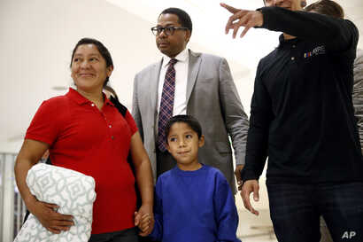Darwin Micheal Mejia, bottom center, and his mother, Beata Mariana de Jesus Mejia-Mejia, left, are escorted to a news conference following their reunion at Baltimore-Washington International Thurgood Marshall Airport, June 22, 2018, in Linthicum, Md....