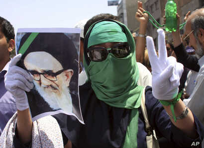 FILE - In this photo, obtained by the AP outside Iran, a female supporter of the Iranian opposition leader Mir Hossein Mousavi flashes a victory sign as she wears a green head scarf, a symbolic color of Mousavi's supporters, while she holds a poster ...