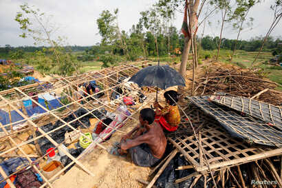 Rohingya refugees sit in front of their house which has been destroyed by Cyclone Mora at the Balukhali Refugee Camp in Cox's Bazar, Bangladesh May 31, 2017.