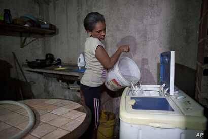 Carmen Rivero fills her washing machine with a bucket of water at her home during water shortages in the Petare shantytown of Caracas, Venezuela, June 7, 2018.