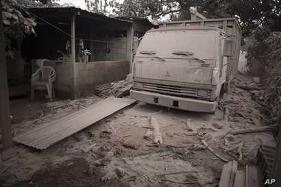 A truck is covered in volcanic ash spewed by volcano El Fuego, or Volcano of Fire, in Escuintla, Guatemala, June 4, 2018.