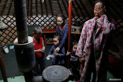 The wife and children of Setevdorj Myagmartsogt gather around their new coal burning stove while talking to reporters in their tent-like ger home in Ulaanbaatar, Mongolia, Jan. 29, 2017.