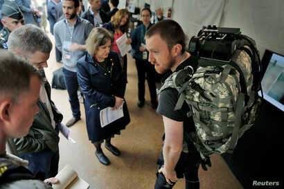 Visitors looks at the lightweight undersuit to reduce injuries & fatigue equipment during the DARPA (Defense Advanced Research Projects Agency) Demo Day exhibition at the Pentagon in Washington, May 11, 2016.