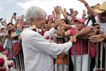 Mexican presidential candidate Andres Manuel Lopez Obrador greets supporters during a campaign rally, in Cancun, June 26, 2018.