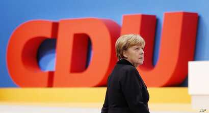 German Chancellor Angela Merkel walks past the logo of her party during a convention of the Christian Democratic Union (CDU) in Karlsruhe, Germany, Dec. 14, 2015.