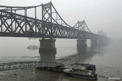 FILE - Trucks move across the bridge linking North Korea with the Chinese border city of Dandong, March 3, 2016. China has banned imports of gold and rare earths from North Korea as well as exports to the country of jet fuel and other oil products us