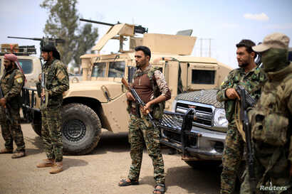 FILE - Fighters of Syrian Democratic Forces (SDF) stand guard in Deir al-Zor, Syria, May 1, 2018.