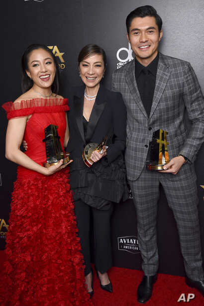 "FILE - From left, Constance Wu, Michelle Yeoh and Henry Golding, winners of the Hollywood breakout ensemble award for ""Crazy Rich Asians,"" are pictured in the press room at the Hollywood Film Awards, Nov. 4, 2018, at the Beverly Hilton Hotel in Bever..."