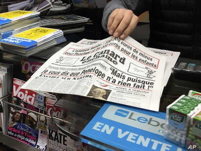 """A newsstand owner picks up a copy of the satirical newspaper Canard Enchaine, or """"The Chained Duck"""" in Paris, Feb. 1, 2017. The dirt-digging weekly claims that conservative presidential candidate Francois Fillon's political clout helped secure handso..."""