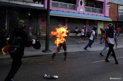 A man who was set on fire by people accusing him of stealing during a rally against President Nicolas Maduro runs amidst opposition supporters in Caracas, Venezuela, May 20, 2017.