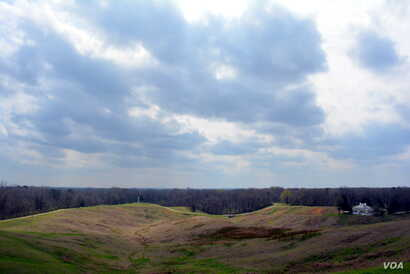 "This photograph taken at Vicksburg National Military Park shows the ""no man's land"" area between Confederate and Union Lines. The white column in the far distance is one of many state monuments that honor the fallen soldiers from that state."