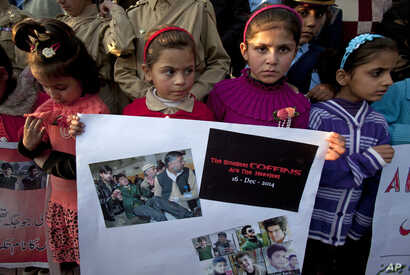Pakistani children hold a placard showing pictures of Peshawar's school attack victims during a demonstration in connection with first anniversary of the school attack, Dec. 15, 2015. Pakistani Taliban militants attacked an army-run school in Peshaw