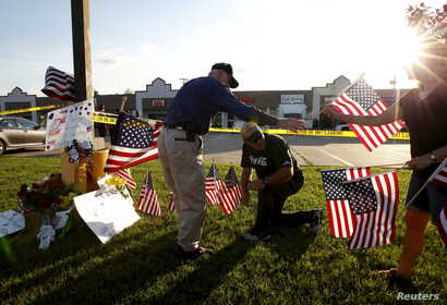 Mourners places flags at a growing memorial in front of the Armed Forces Career Center in Chattanooga, Tennessee, July 16, 2015.