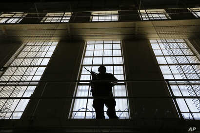 A guard stands watch over death row at San Quentin State Prison in California. A pair of November ballot measures will decide the future of the death penalty in that state.