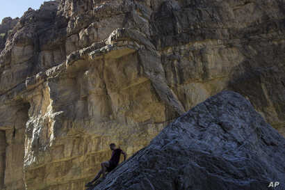 A man descends a rock on the bank of the Rio Grande, just a few feet from a cliff wall that is Mexico, in Santa Elena Canyon, at Big Bend National Park in Texas, March 27, 2017.