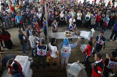 Displaced residents of Marawi city prepare to receive food packs and sleeping mats from the International Committee of the Red Cross at an evacuation center in Saguiaran township near the besieged city of Marawi, in southern Philippines, May 28, 2017...