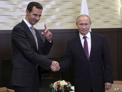 FILE - On this Nov. 20, 2017 file photo, Russian President Vladimir Putin, right, shakes hands with Syrian President Bashar Assad in the Black Sea resort of Sochi, Russia.