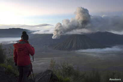 A visitor takes photographs of Mount Bromo, an active volcano and popular tourist destination, in Probolinggo, East Java province, Indonesia April 3, 2016 in this photo taken by Antara Foto.
