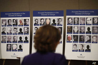 An advocate and survivor of sexual abuse, looks at the photos of Catholic priests accused of sexual misconduct by victims during a news conference, Dec. 6, 2018, in Orange, California.