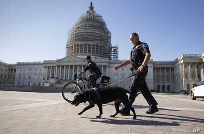 U.S. Capitol Police officers keep watch over the East Front of the Capitol as Congress prepares to return to work following the weekend terror attacks in Paris that killed 129 people, in Washington, Nov. 16, 2015.