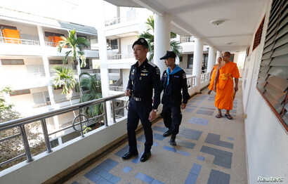 Policemen and Buddhist monks search for a fugitive Buddhist monk inside Dhammakaya temple in Pathum Thani province, Thailand, Feb. 17, 2017.