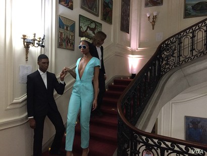 """Model wears sexy jumpsuit from designer Prajje Oscar's """"Ezili"""" collection at the Haitian Embassy's """"Fashion By Design"""" event in Washington, D.C. Feb. 23, 2018. (Photo: S. Lemaire / VOA)"""