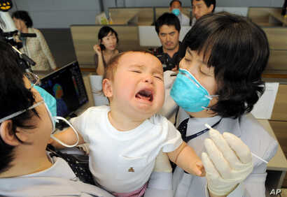 FILE - South Korean quarantine officers try to take samples of a baby arriving from the US at Incheon airport, west of Seoul.