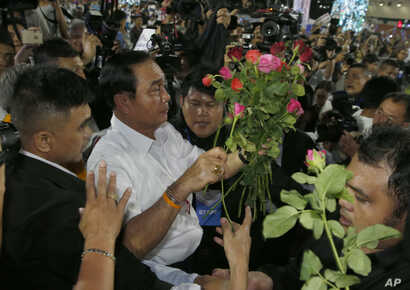 Prayuth Chan-ocha of the Palang Pracharat Party receives flowers from supporters during an election campaign rally in Bangkok, Thailand, March 22, 2019.