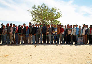 Bangladeshi migrant workers line up for food at the refugee camp 25km from the Libyan border.