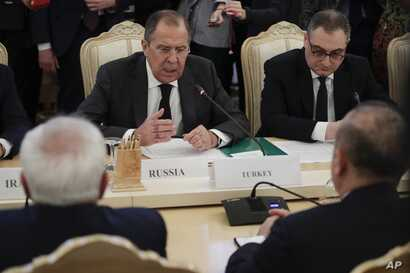 Russian Foreign Minister Sergey Lavrov, center, gestures while speaking to Turkey's Foreign Minister Mevlut Cavusoglu, right, back to a camera, and Iranian Foreign Minister Mohammad Javad Zarif, left, back to a camera, during their talks in Moscow, R...