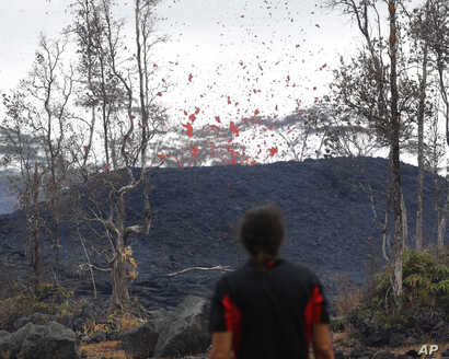 Abe Pedro watches lava shoot from a fissure on Pohoiki Road, May 18, 2018, near Pahoa, Hawaii.