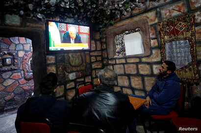 Palestinians watch a televised broadcast of Palestinian President Mahmoud Abbas' speech, in the West Bank city of Nablus, Dec. 6, 2017.