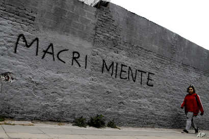 """A woman walks past a wall spray-painted with a message that reads in Spanish """"Macri lies"""" in reference to the country's president, Mauricio Marci, in Buenos Aires, Argentina, Aug. 30, 2018. Argentina's Central Bank on Thursday increased its benchma..."""