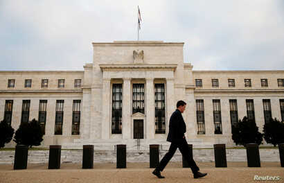 FILE - A man walks past the Federal Reserve Bank in Washington, D.C.