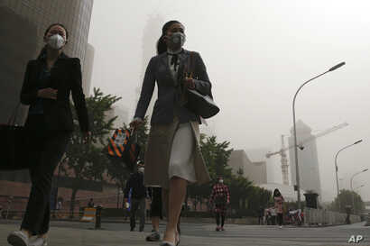 Office workers wearing face masks walk on a street as Beijing is hit by polluted air and sandstorm, May 4, 2017.