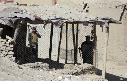 Policemen inspect an area after a bomb explosion near a polling station in Kabul, Afghanistan, Oct. 20, 2018.