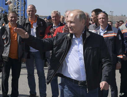 Russian President Vladimir Putin gestures while speaking to a group of workers after driving a truck to officially open the much-anticipated bridge linking Russia and the Crimean peninsula the opening ceremony near in Kerch, Crimea, Tuesday, May 15, ...