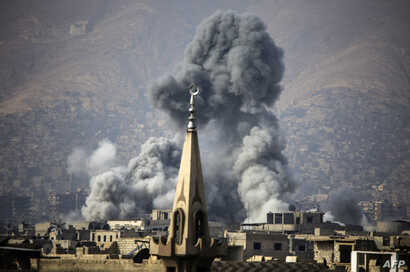 A picture taken on November 23, 2017 shows smoke rising following a reported air strike on the rebel-held besieged town of Arbin, in the Eastern Ghouta region on the outskirts of Damascus.