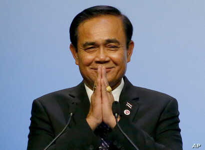 Thai Prime Minister Prayuth Chan-ocha gestures the Thai way shortly after accepting the ASEAN Summit and Related Summits' hosting and chairmanship for next year in Thailand from Singaporean Prime Minister Lee Hsien Loong, in Singapore, Nov. 15, 2018....