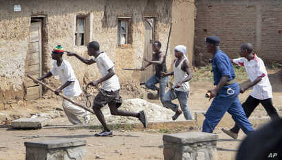 Members of the Imbonerakure pro-government youth militia chase after opposition protesters, unhindered by police, in the Kinama district of the capital Bujumbura, in Burundi Monday, May 25, 2015. Protests continued in the capital Monday, with demonst