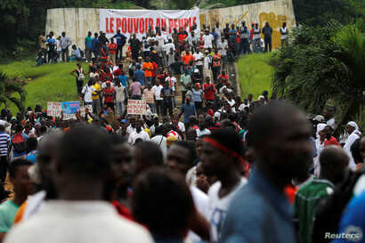 "Supporters of Ivory Coast's opposition hold placards as they protest during a political rally ahead of the referendum on a new constitution, in Abidjan, Ivory Coast October 28, 2016.The banner in the background reads ""power to people"". REUTERS/Luc Gn..."