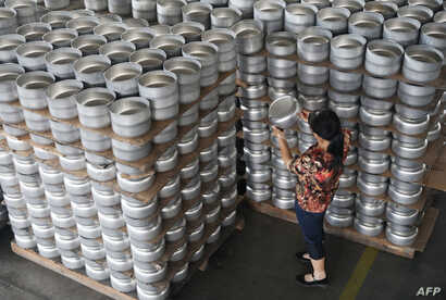 FILE - An employee checks pots that will be exported to South Africa at a factory in Hangzhou in China's eastern Zhejiang province, June 25, 2018.