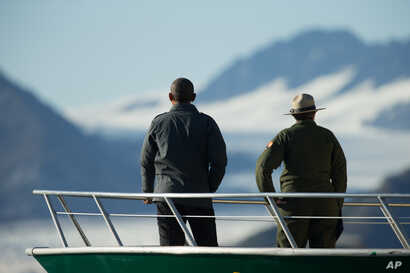 President Barack Obama, accompanied by a National Park Service employee looks at Bear Glacier, which has receded 1.8 miles in approximately 100 years, while on a boat tour to see the effects of global warming in Resurrection Cove, Sept. 1, 2015, in S...