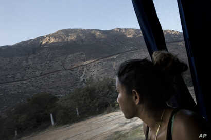 A Central American migrant looks out toward the border with the U.S., between Mexicali and Tijuana, as she rides by bus with a caravan of migrants to Tijuana, Mexico, April 26, 2018.