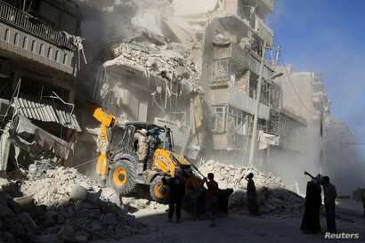 A front loader removes debris in a damaged site after airstrikes on the rebel held Tariq al-Bab neighbourhood of Aleppo, Syria, Sept. 24, 2016.