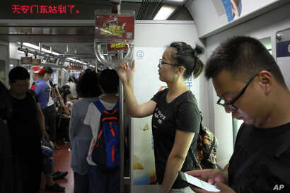 Ren Liping, second right, takes a subway train to the police headquarters to file her petition after arriving in Beijing.
