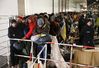 Migrants queue on a street to enter the compound outside the Berlin Office of Health and Social Affairs (LAGESO) for their registration process in Berlin, Germany, in this Dec. 9, 2015 file picture.