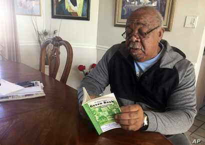 """Charles Becknell, Sr., 77, holds a copy of 1954 the edition of """"The Negro Motorist Green Book"""" at his home in Rio Rancho, N.M., Jan. 31, 2019."""